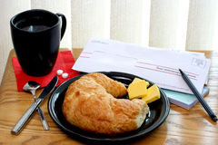 Croissant, Coffee and Bills. Table setting showing fresh breakfast croissant, cup of coffee, two aspirin and bills to pay Royalty Free Stock Photo