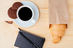 Croissant, coffee and black notebook on wooden table Royalty Free Stock Image