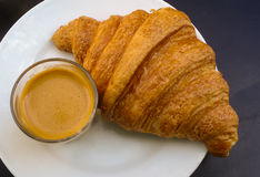 Croissant and coffee breakfast on a white plate. Golden croissant and coffee continental breakfast on a white plate Royalty Free Stock Photo