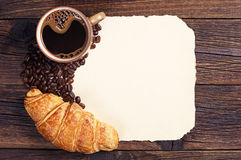 Croissant, coffee cup and old paper. Croissant and cup of hot coffee and blank sheet of old paper as a background, top view Royalty Free Stock Photography