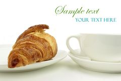 Croissant and coffee cup on white background.  Royalty Free Stock Image