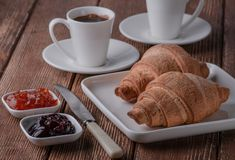 Croissant with coffee and jam made of cherry and apricot. royalty free stock photo