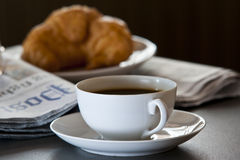 Croissant, coffee, newspaper with glasses Stock Photos