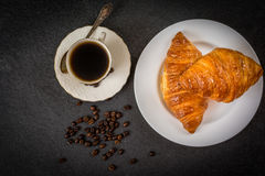 Croissant and coffee. Traditional french breakfast croissant and coffee on black stone table top view Stock Image