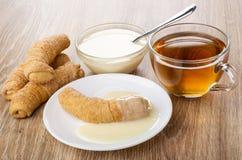 Croissant com leite condensado em pires, croissant, colher na bacia com leite, copo do chá na tabela fotos de stock royalty free