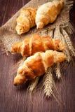 Croissant com os spikelets do trigo no fundo de madeira Fotos de Stock Royalty Free