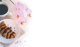 Croissant con cioccolato, la tazza di caffè e un'orchidea rosa su w Immagini Stock