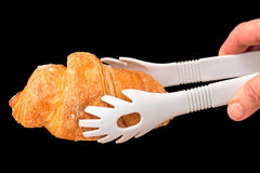 Croissant and Cooking tongs Royalty Free Stock Photography
