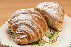 Croissant cortado ao meio em um prato Imagens de Stock Royalty Free