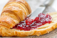 Croissant with cranberry jam closeup. Royalty Free Stock Photography