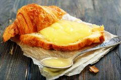 Croissant with cream and teaspoon. Stock Photo