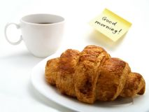 A croissant, a cup of coffee and a yellow note Stock Photography