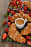 Croissant and a cup of espresso. On a wooden background Stock Photography