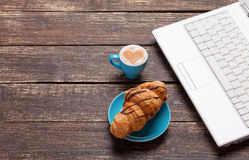 Croissant and cup with laptop Royalty Free Stock Images