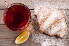 Croissant with a cup of tea on old wooden background. Top view Stock Images