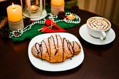 Croissant de chocolat du plat et de la tasse blancs de cappuccino Photographie stock
