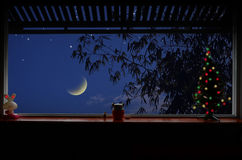Croissant de lune et étoiles la nuit dans la vue de fenêtre Photos stock