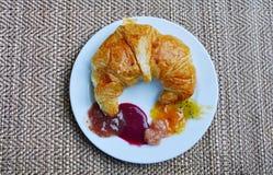 Croissant del burro ed inceppamento ordinato sul piatto immagini stock libere da diritti
