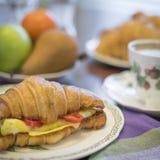 Croissant del formaggio e dell'uovo con frutta e caffè Immagini Stock Libere da Diritti