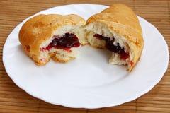Croissant die half en half op een plaat wordt gebroken Stock Foto's