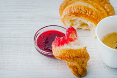 Croissant dipped in berry jam with cup of coffee Royalty Free Stock Photography