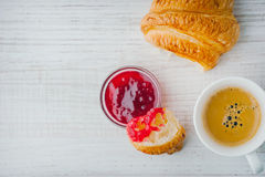 Croissant dipped in berry jam with cup of coffee top view Stock Photo