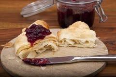 Croissant diviso in due con la marmellata d'arance della ciliegia sul piatto di legno Fotografie Stock