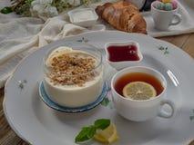 Croissant, doce, chá com limão, em um prato de porcelana imagens de stock