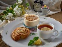 Croissant, doce, ch? com lim?o, em um prato de porcelana foto de stock