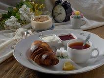 Croissant, doce, ch? com lim?o, em um prato de porcelana imagem de stock royalty free