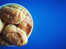 Croissant doces na placa no fundo azul Fotografia de Stock Royalty Free