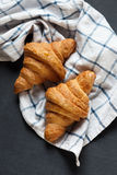 Croissant dois fresco que encontra-se em um quadro-negro Também, há toalha de linho torcida Imagens de Stock