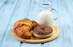 Croissant, donut and milk jug on a wooden background. Croissant, donut and milk jug on a light blue wooden background Royalty Free Stock Photos