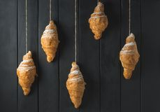 Croissant dorati su fondo di legno nero rustico fotografia stock