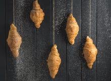 Croissant dourados no fundo de madeira preto fotos de stock