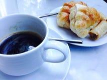 Croissant doux et une cuvette de café à l'arrière-plan Photographie stock