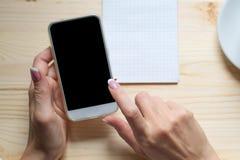 Croissant doux et une cuvette de café à l'arrière-plan Les mains femelles touche un écran au téléphone intelligent, manucure fran images stock