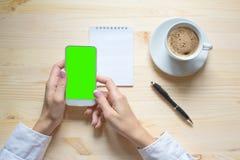Croissant doux et une cuvette de café à l'arrière-plan Mains femelles utilisant le téléphone intelligent, bloc-notes, stylo, tass photo libre de droits