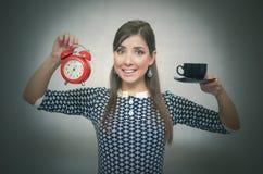 Croissant doux et une cuvette de café à l'arrière-plan Temps de café Pause de midi Fille avec la tasse du café et du réveil rouge photo libre de droits
