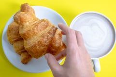 Croissant e cacao o cioccolata calda caldo su un fondo giallo, vista superiore, prima colazione fotografie stock