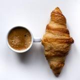 Croissant e caffè espresso su fondo bianco Fotografia Stock