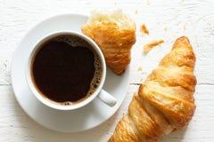 Croissant e caffè su legno bianco rustico, da sopra immagine stock