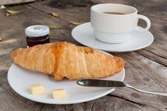 Croissant e caffè sulla tavola di legno Fotografie Stock Libere da Diritti