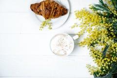 Croissant e cappuccino del cioccolato, decorati con il fiore della mimosa fotografia stock