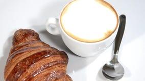 Croissant e cappuccino su una rotazione bianca del piatto video d archivio