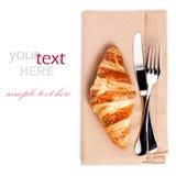 Croissant e cuttery no guardanapo de linho isolado no backgrou branco Imagem de Stock