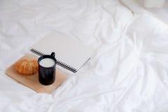 Croissant e libro sulla tavola di funzionamento di mattina Immagine Stock Libera da Diritti