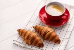 Croissant e tazza di caffè su una tavola di legno bianca fotografie stock libere da diritti