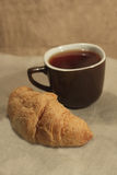 Croissant e um copo do chá Foto de Stock