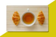 Croissant e um copo do chá em uma bandeja de madeira fotografia de stock royalty free